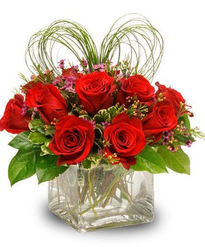 Rich red roses mounded delicately in a cube style vase.